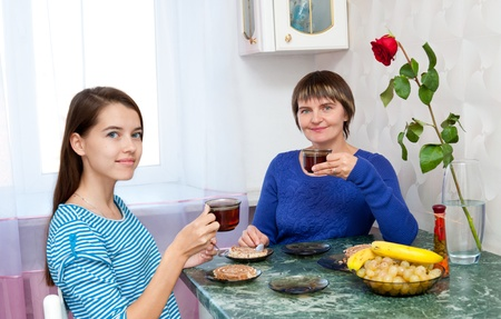 a mother and her daughter have tea photo