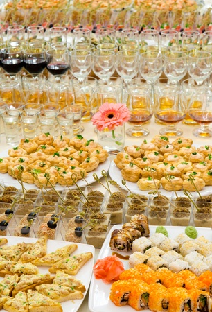 a lot of cold snacks and drinks on buffet table, catering photo