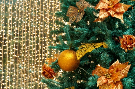 fragment of christmas tree with gilt ball and flowers photo