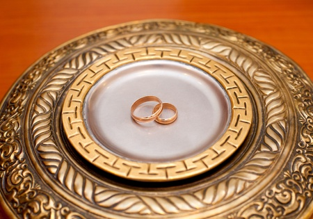 solemnization: two plain golden wedding rings on a copper salver Stock Photo