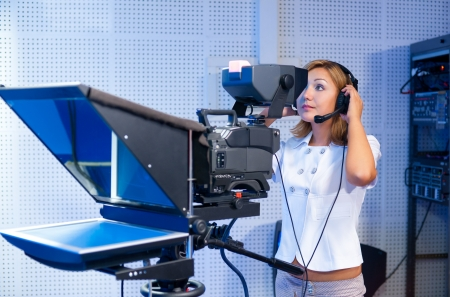 camera operator: a woman cameraman at a TV studio during live broadcasting