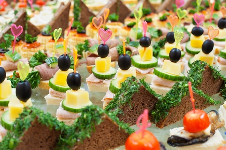 a lot of canapes with skewers on a buffet table photo