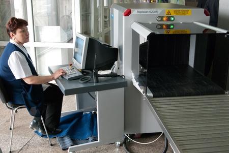 op maat: ULAN-UDE, RUSLAND - APRIL 2: De stad luchthaven opent internationale luchtroutes en dus een douane-station op 2 april 2009, Ulan-Ude, Boerjatië, Rusland. Unidentified veiligheid operator scant bagage. Redactioneel