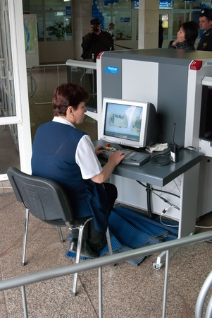 airport security: ULAN-UDE, RUSSIA - APRIL 2: The city airport opens international air routes and consequently a customs station on April 2, 2009, Ulan-Ude, Buryatia, Russia. Unidentified safety operator scans luggage.