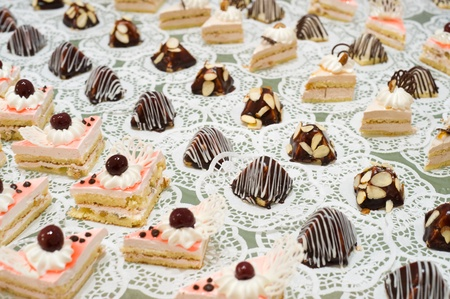 buffet table: many cream sponge cakes and tapered sweets on buffet table