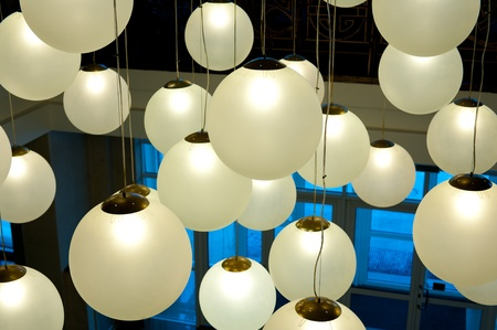 lampshade: many round ceiling lamps hang at different height Stock Photo