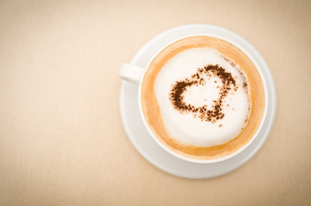 capuccino: cup of cappuccino coffee, chocolate heart on top, copy space