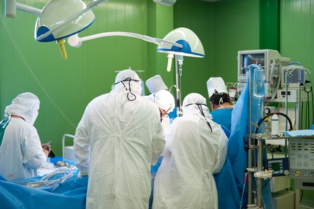 operation gown: a real surgical operation in a green room Stock Photo