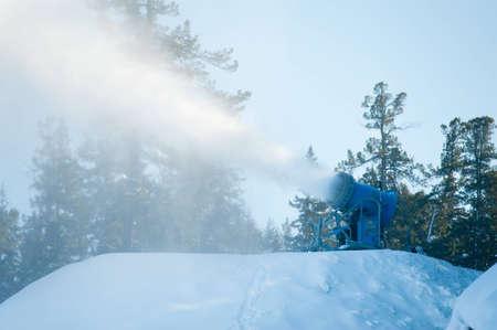 a snow gun makes snow at a hill top  at a ski resort  photo