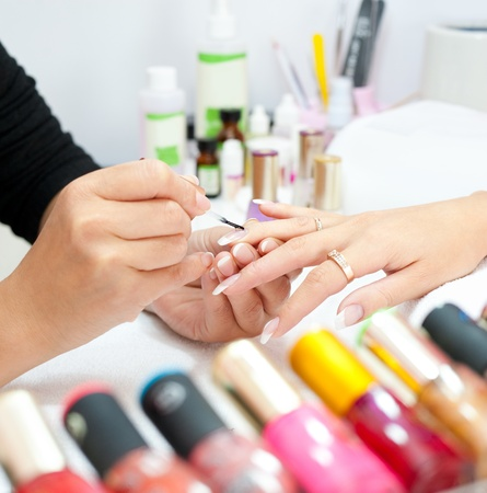 manicure making - female hands, rows of colored enamel phials in the foreground Stock Photo - 12540718