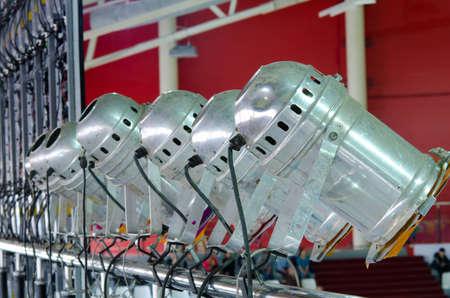 inoperative: a line of metal spotlights in an indoor stadium Stock Photo