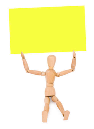 inanimate: a wooden sitting man holds a yellow note paper, over white background Stock Photo