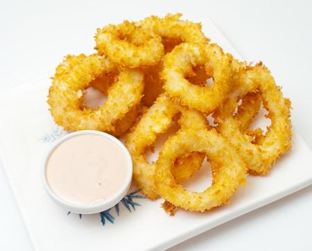 calamar: anillos de calamar, fritos en masa con un tazón la mayonesa Foto de archivo