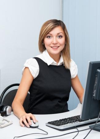 economia aziendale: una giovane donna caucasica seduta davanti a un computer guarda in camera e sorride Archivio Fotografico