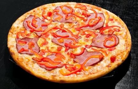 a pizza with meat and red paprika Stock Photo - 12540693