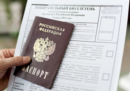 elective: a hand holds a passport and a ballot for voting at the presidential election of Russian Federation, closeup Stock Photo