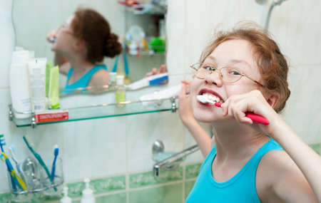 upper half: a 10 year old girl brushes her teeth