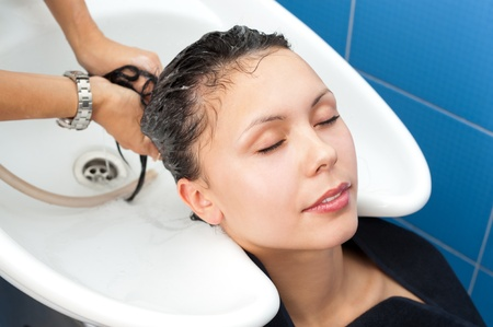 hair conditioner: hair washing at a hairdressing salon, young caucasian brunette Stock Photo