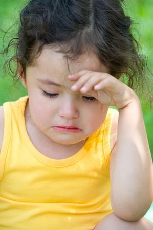 a cute 4 year old girl cries, closeup photo