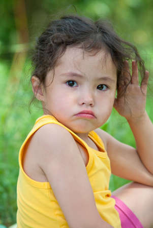 a cute 4 year old girl in tears looks angrily into camera photo