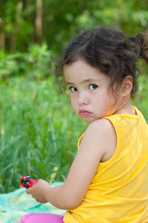 an offended 4 year old girl in tears looks into camera photo