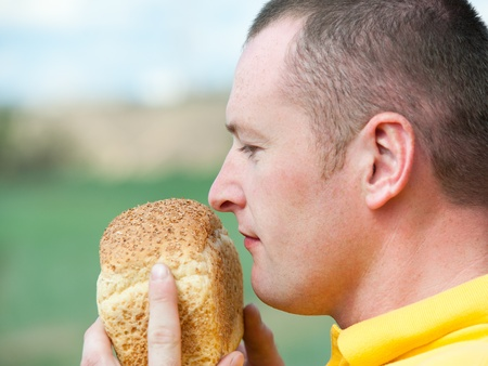 bestrew: a young caucasian man smells odour of fresh bread