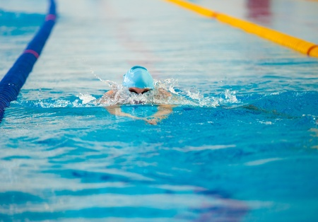 moving activity: a swimmer swims in an indoor pool Stock Photo