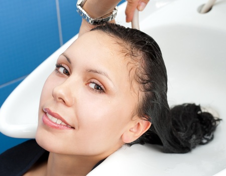 haren wassen bij een kapsalon, een brunette jonge Kaukasische