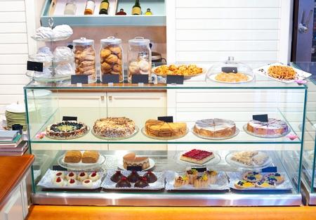 bij een banketbakkerij - een glazen vitrine met desserts Stockfoto