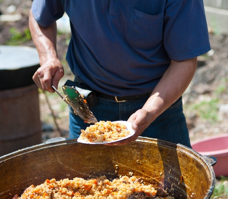 caldron: a man puts pilau  oriental spicy rice with lamb , cooked in open air Stock Photo