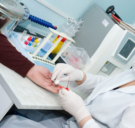 a nurse collects a blood specimen from a finger photo