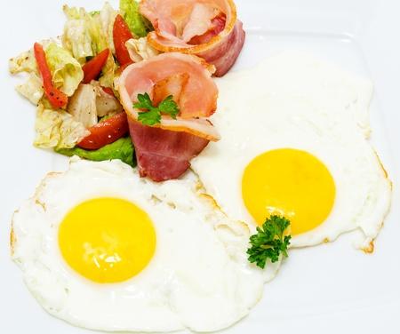 huevos fritos: tocino frito y los huevos con ensalada de verduras