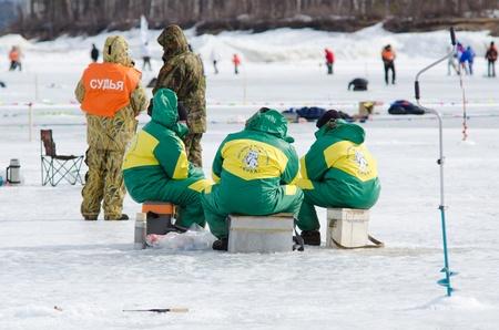 sit around: YARTSI, RUSSIA - APRIL 14  A team of fishers from Kika village sit around their ice hole during Baikal Fishing 2012, April 14, 2012 in Yartsi, Buryatia, Russia