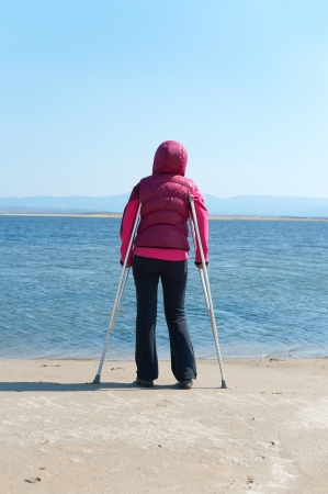 a woman stands on crutches at a lake shore, back view photo