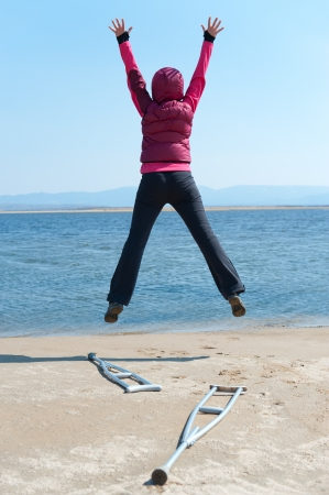 a woman jumps, having left her crutches, at a lake shore, back view photo