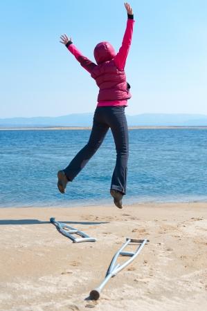 beine spreizen: eine glückliche Frau springt, nachdem sie verließ ihren Krücken, an einem Seeufer, Blick zurück