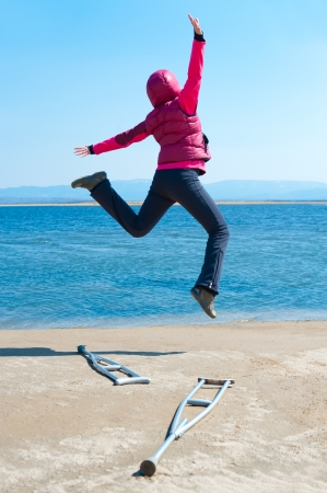 a happy woman jumps, having left her crutches, at a lake shore, back view photo