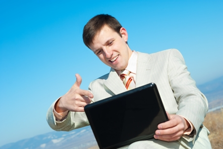 a smiling businessman points to a laptop screen Stock Photo - 13851765