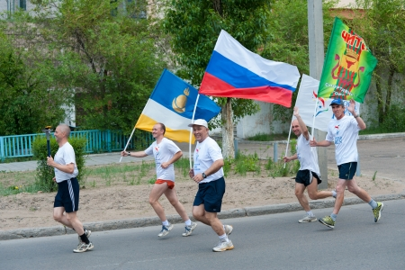 ulan ude: ULAN-UDE, RUSSIA - JUNE 11  Unidentified volunteers of World Harmony Run run carrying a torch, a symbol of harmony, flags of WHR, Russia, Buryatia, Chita, June, 11, 2012, Ulan-Ude, Buryatia, Russia