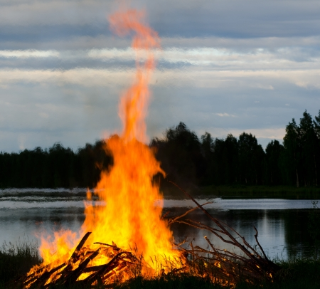 midsummer: a big fire at a lake shore on Midsummer Day, Finland Stock Photo