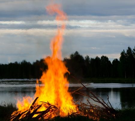 resplandor: un gran incendio en una orilla del lago en verano Día, Finlandia Foto de archivo