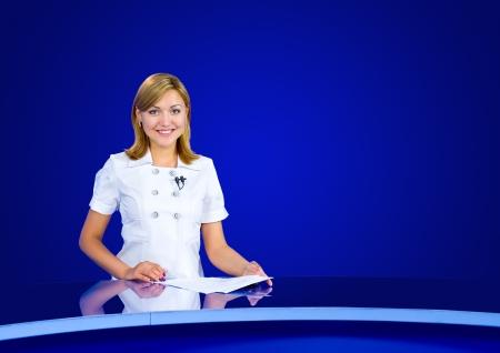 een televisie anchorwoman op een lege blauwe studio Stockfoto