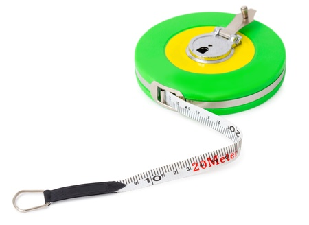 a measuring tape in a green reel, over white  photo
