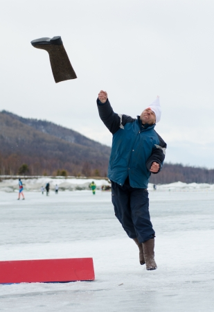 YARTSI, RUSSIA - APRIL 14  At annual Baikal Fishing Valenok Throwing was run, Apr 14, 2012, Yartsi, Buryatia, Russia  An unidentified man makes his throw