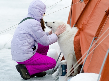 squatter: a teenage girl pats a white dog by a tent