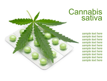 sativa: a leaf of marijuana  Cannabis sativa  on a blister with green drugs Stock Photo