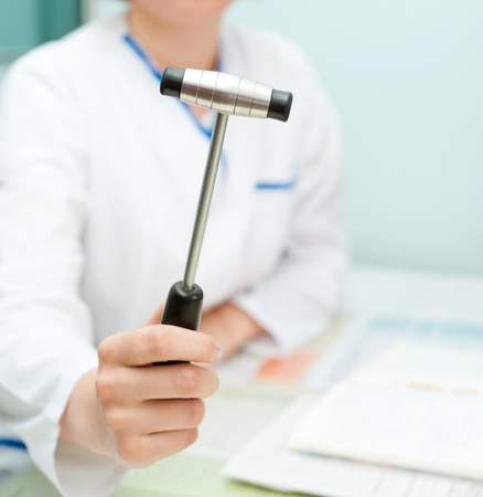 public insurance: a doctor neuropathologist shows a reflex hammer to camera