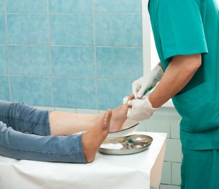 a surgeon cures a sick finger of a patient photo