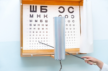testing vision: a Russian eye chart at an oculist and a hand with a pointer
