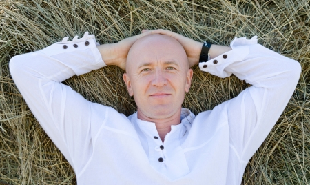 agreeable: a caucasian man in a white shirt smiles lying on hay  Stock Photo